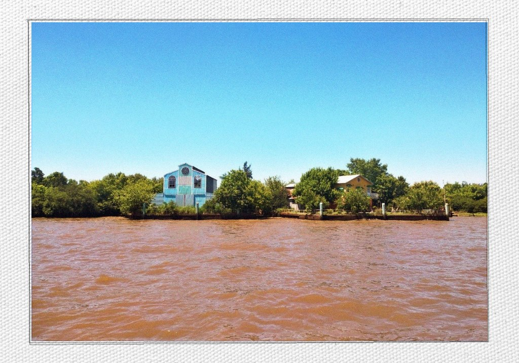The colors of Argentina: a blue sky, wooden houses and water the color of caramel