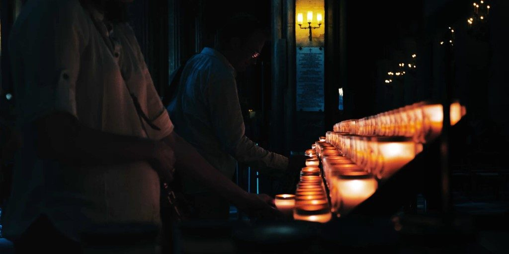 People lighting candles inside Notre Dame (before fire)