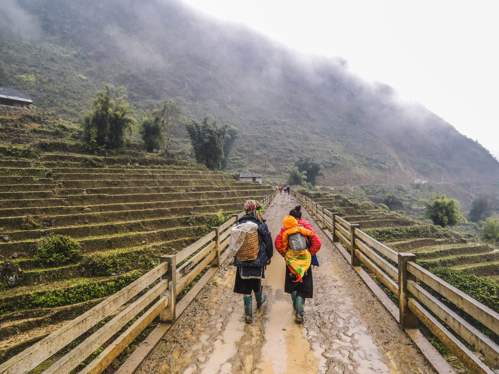 Trekking in Sa Pa Vietnam with two local H'mong women, one is carrying a basket while the other carries a baby