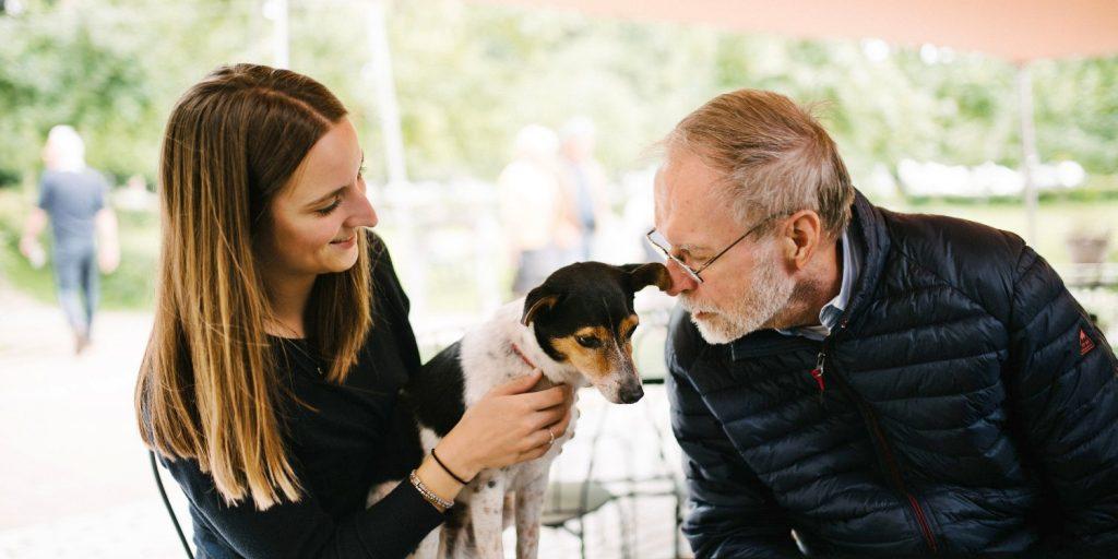 Marjolijn en haar vader aaien een hond