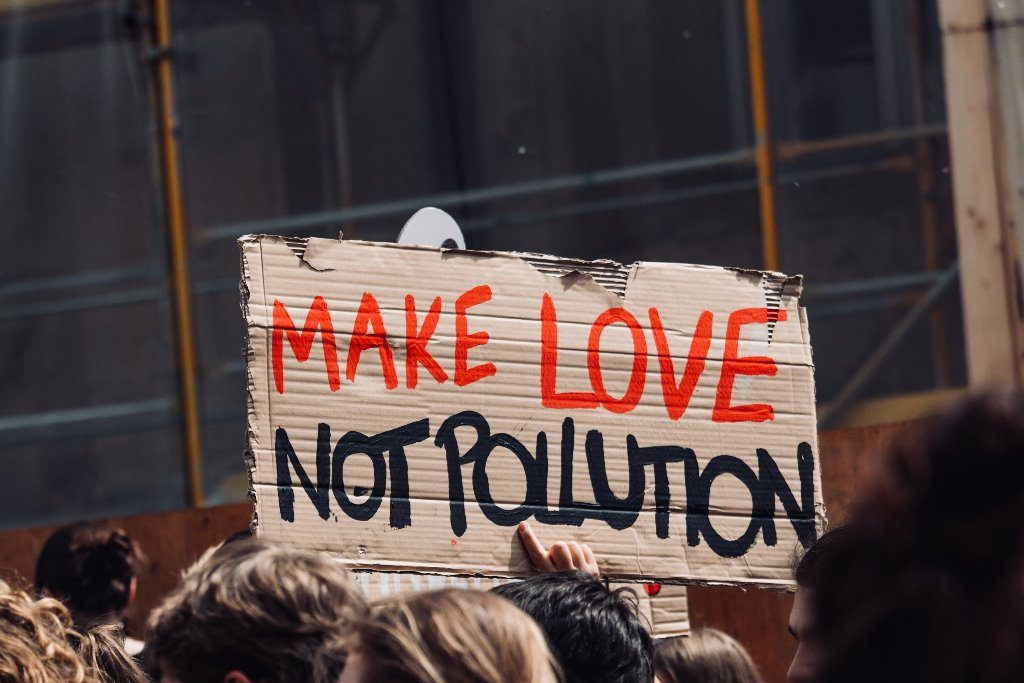 "Somebody holding a sign in a protest that says: ""Make love not pollution""."