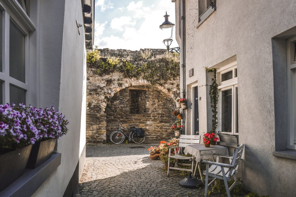 A historic little street with flowers, chairs, and bicycles in the background