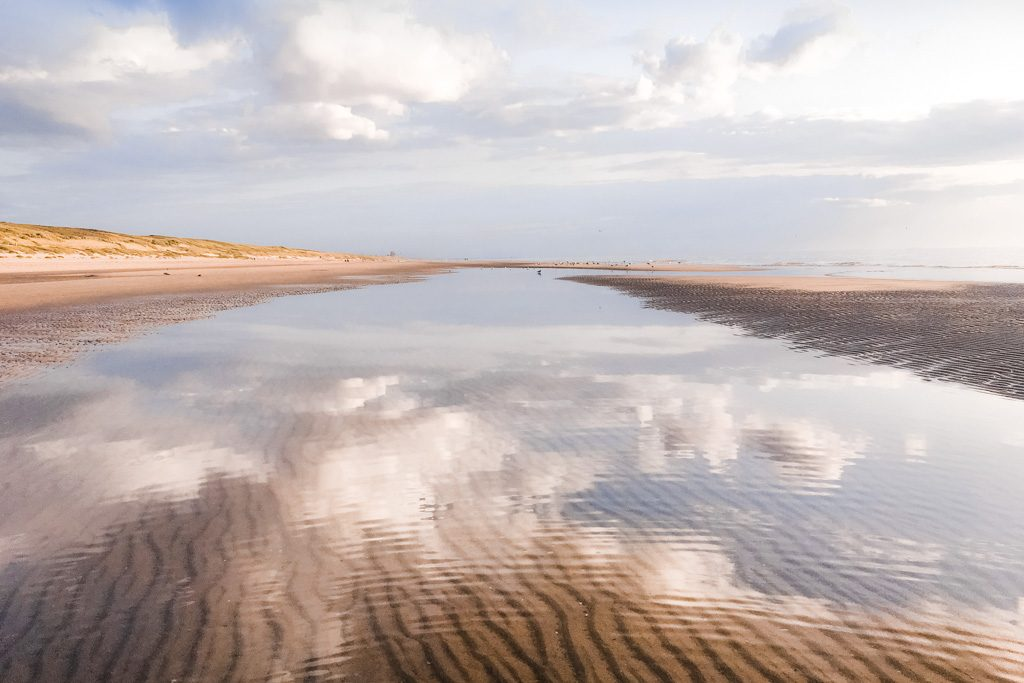 Escapes into nature are one way to feel inspired: clouds reflect in the North Sea at Noordwijk Beach