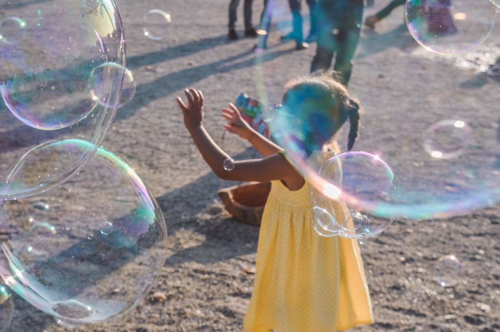 A little girl in a yellow dress chases soap bubbles in Amsterdam