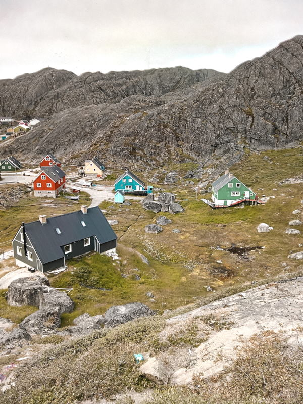 Maniitsoq in summer, Greenland: sporadic colourful houses in the green and rocky landscape.