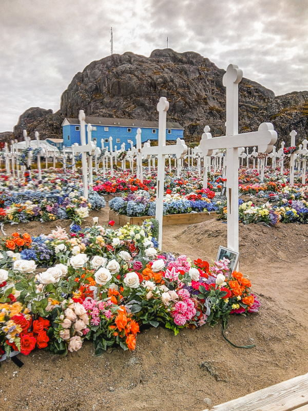 A cemetery in Maniitsoq with wide wooden crosses and an abundance of artificial flowers.