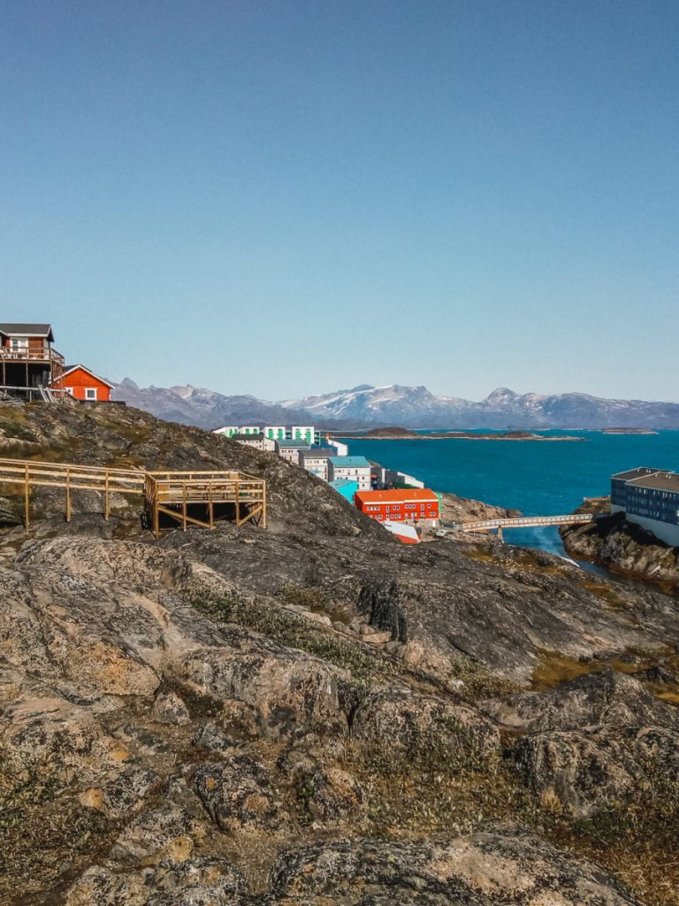 Maniitsoq on a sunny day, with a few colourful houses and a blue sky