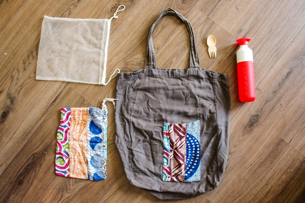 A flatlay of reusable bags and a bottle