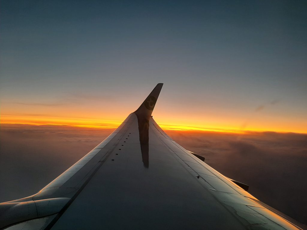 Wing of an airplane with clouds underneath, an orange sunrise and blue sky.