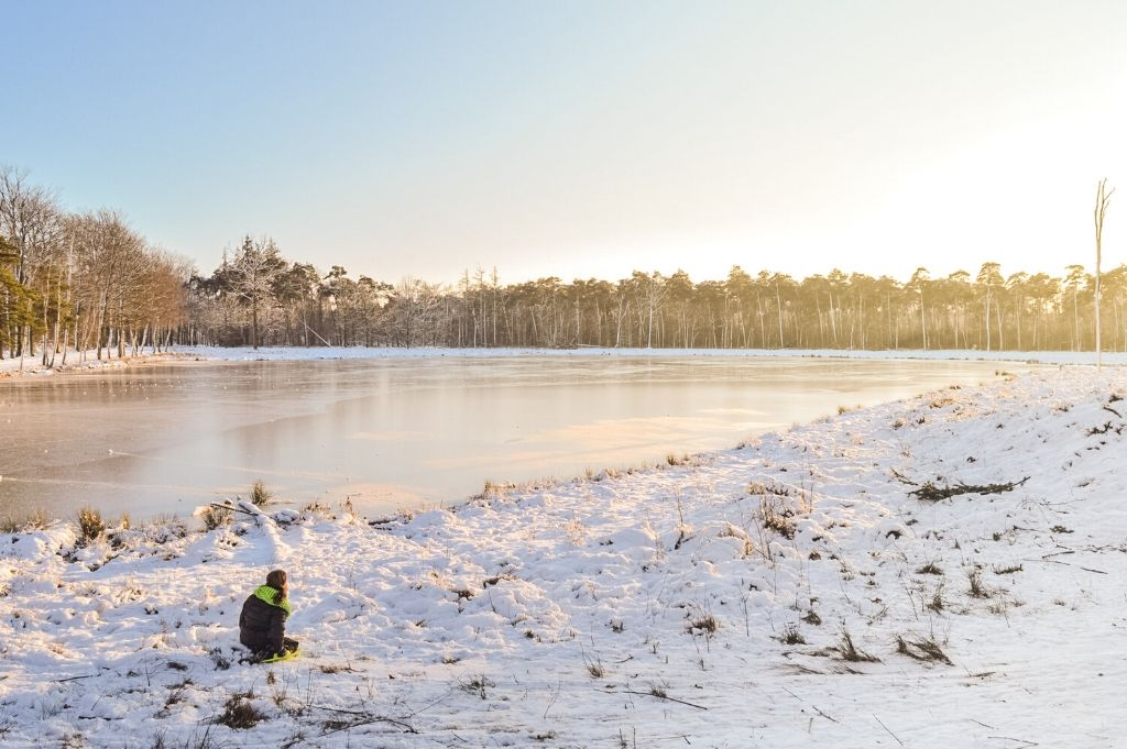 A girl gazes at a frozen lake while kneeling in the snow