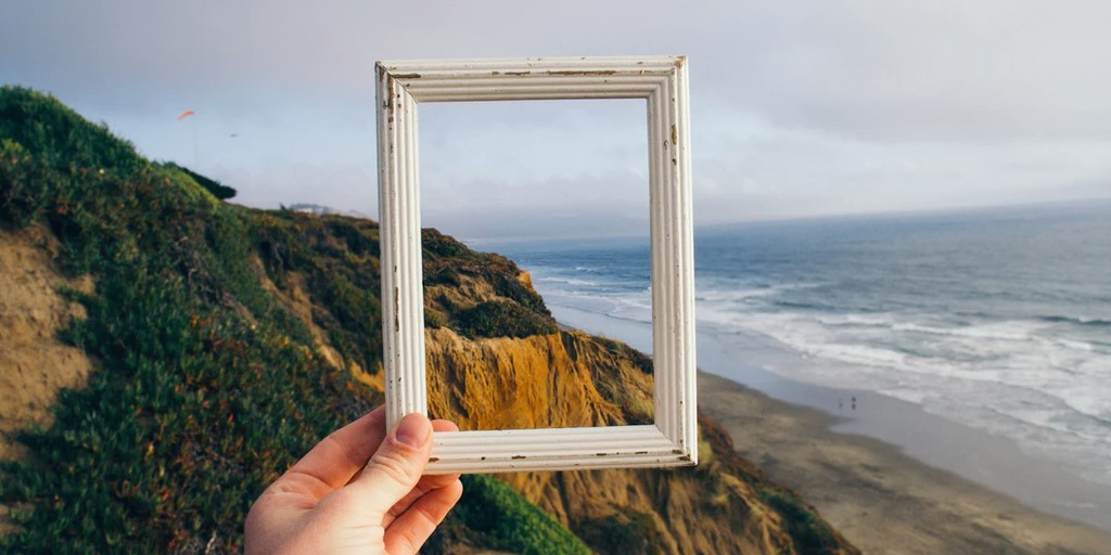 A person holding an empty frame with a natural beach landscape in the background